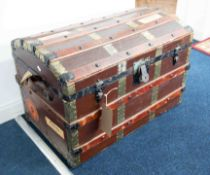 An old cabin trunk, dome top with some shipping labels and fitted with a tray.