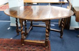 A large heavy oak gate-leg dining table with barley twist legs, together with a set of eight