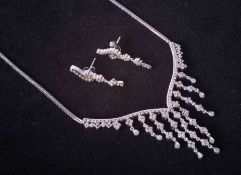 An 18ct white gold graduated style necklace set diamonds together with a pair of matching drop