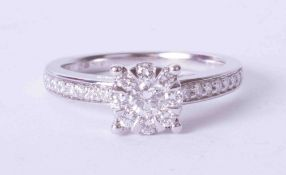 An 18ct white gold diamond set cluster ring with diamonds to the shoulders, finger size M.