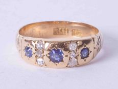 An 18ct yellow gold diamond and sapphire set ring in a gypsy style setting, finger size M.
