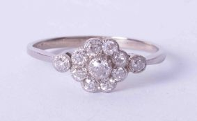 An antique 18ct white gold diamond flower cluster ring with milgrain setting, finger size S.