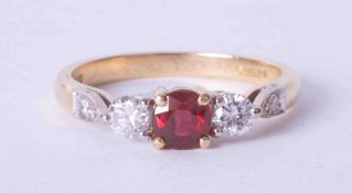 An 18ct yellow gold three stone ring set approx. 0.36 carat ruby and 0.35 carat diamonds (total