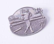 A silver oval golfing scene brooch, 10.7g, approx. 5cm x 4cm.