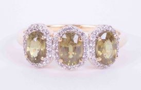 A 9ct yellow gold three stone ring set 1.85 carats of oval demantoid garnet surrounded by 0.30
