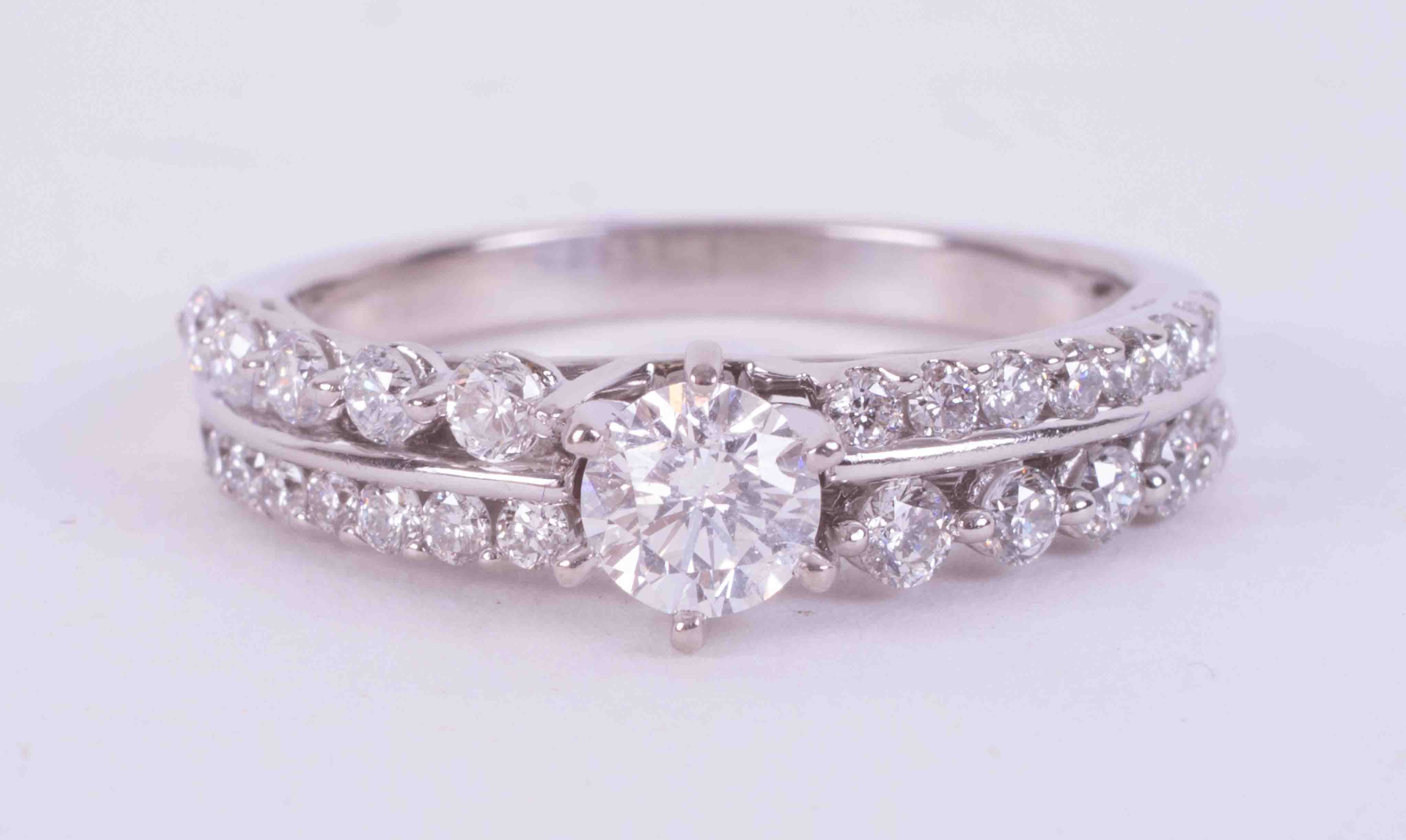 A 14k white gold ornate ring set with a double row of approx. 0.32 carats of round brilliant