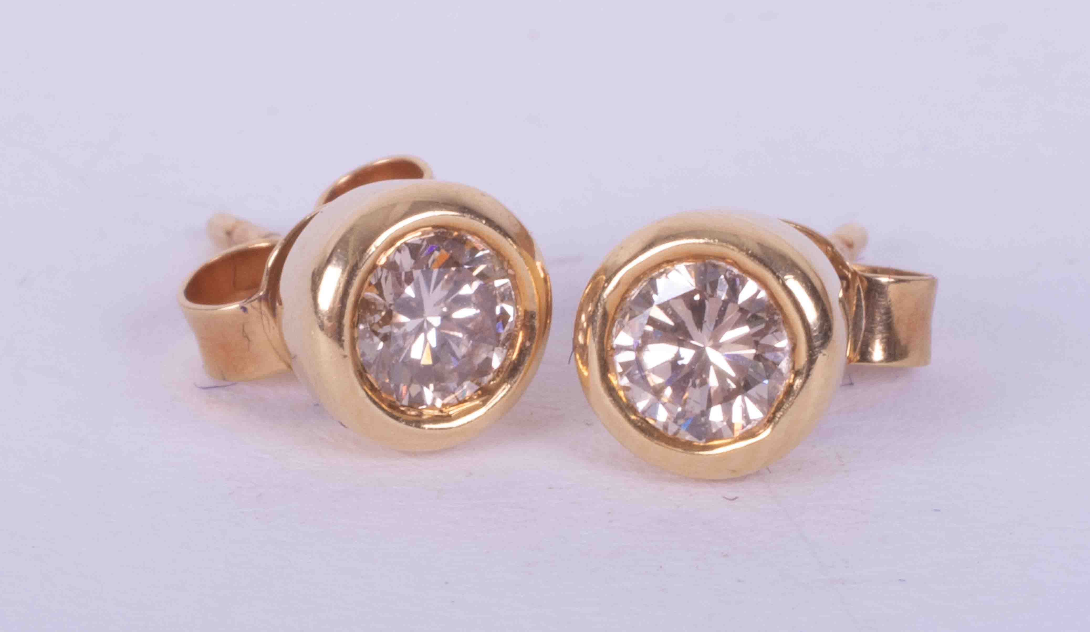 A pair of 18ct yellow gold rub over studs set a total weight of 0.50 carats of round brilliant cut