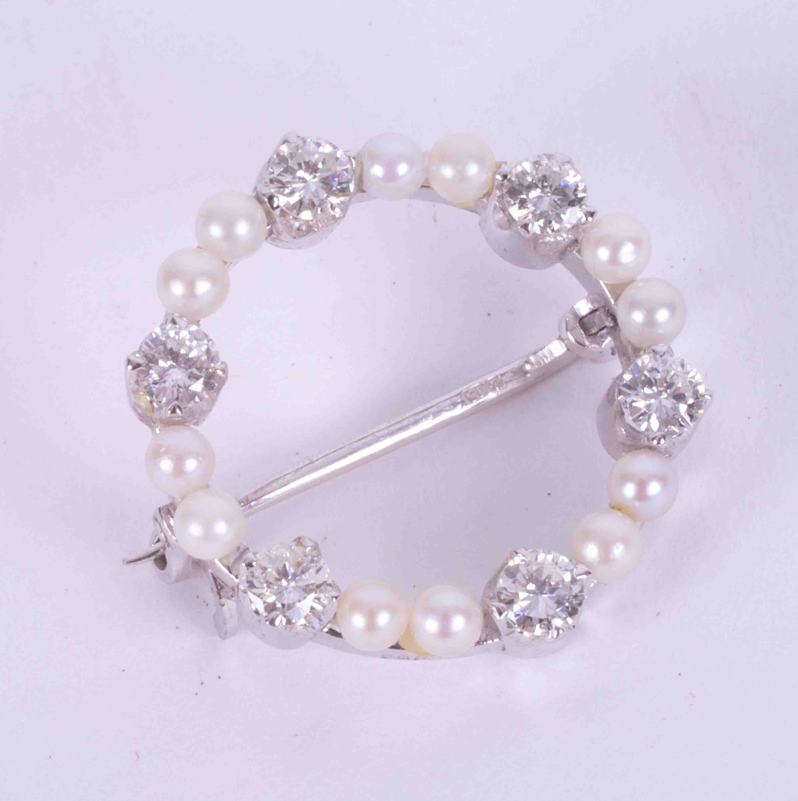 An 18ct white gold circular brooch set with twelve little cultured pearls & six round brilliant