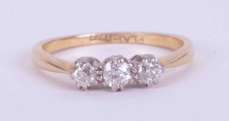 An 18ct yellow gold & platinum three stone ring set with approx. 0.22 carats of round brilliant