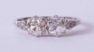 An Art Deco Platinum & 18ct white gold ring set with two central round old cut diamonds each approx.