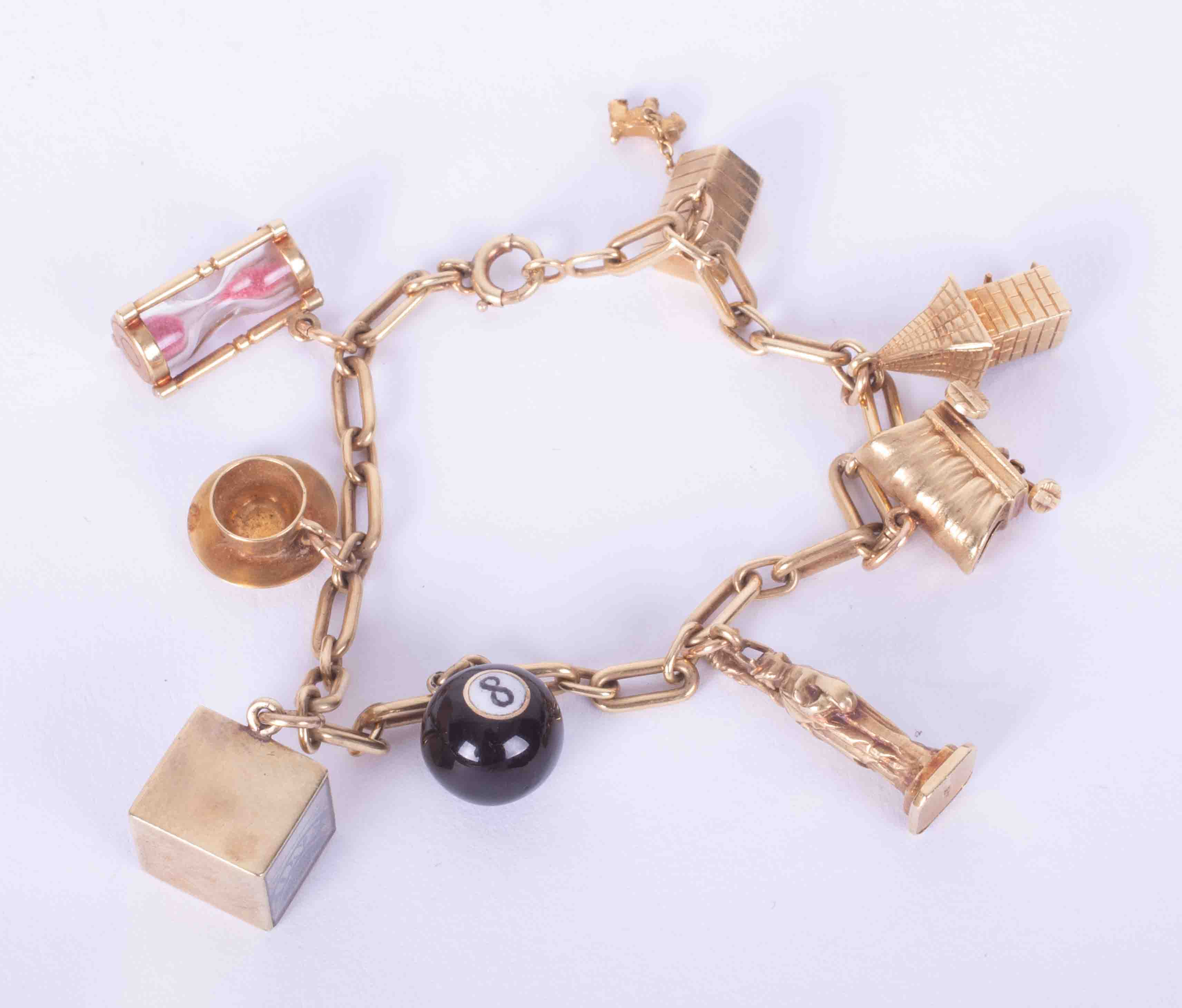 A 14k yellow gold charm bracelet with eight 14k charms to include a snooker ball, Statue of Liberty,
