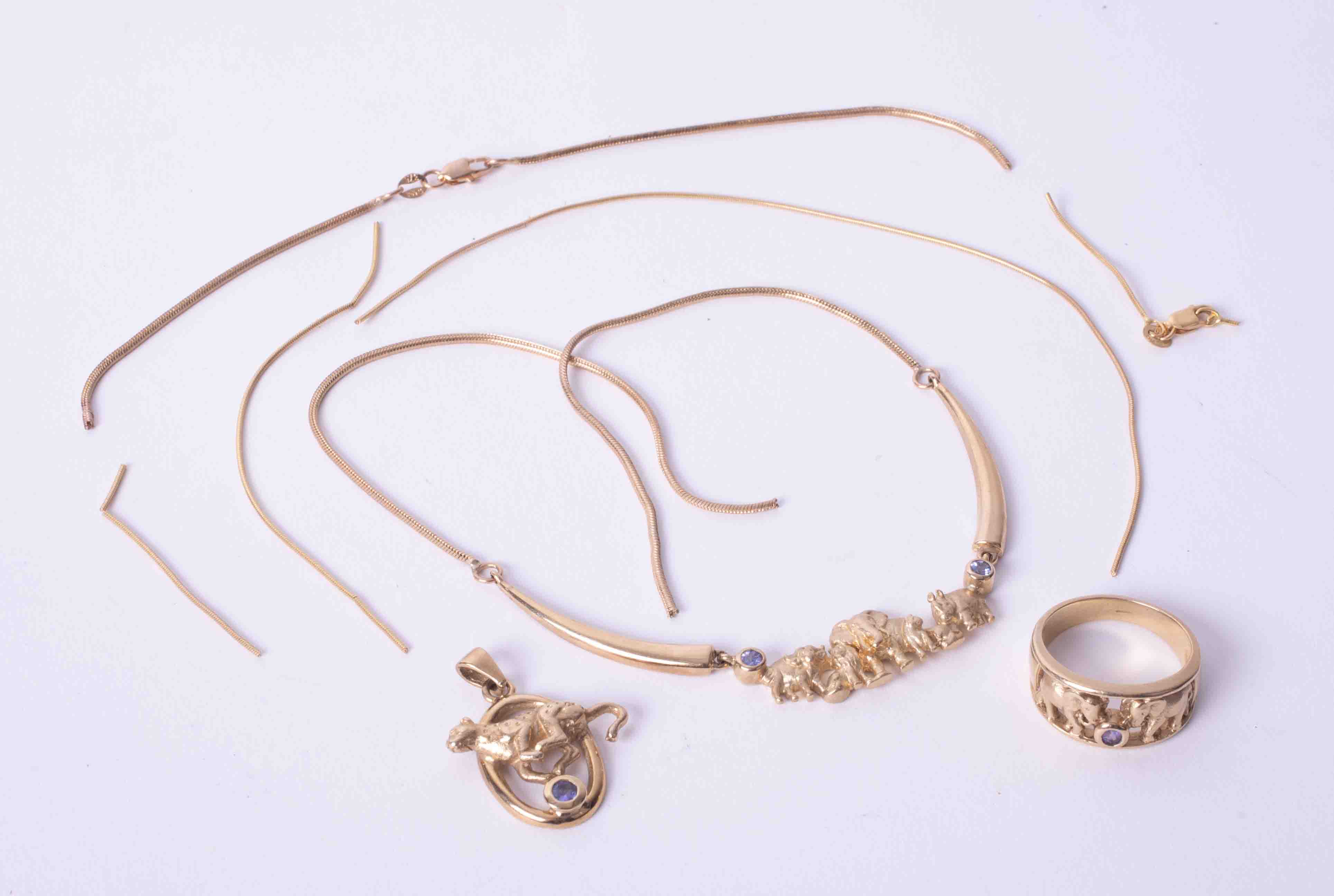 A 9ct gold suite of jewellery including ring, pendant and necklace set with tanzanite and elephants,