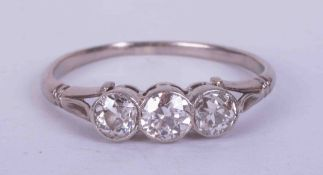 An antique platinum three stone rub over set ring with approx. 0.60 carats total weight of old cut