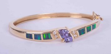 A 14k yellow gold bangle set centrally with two interlocking trilliant cut tanzanite's, approx. 1.40