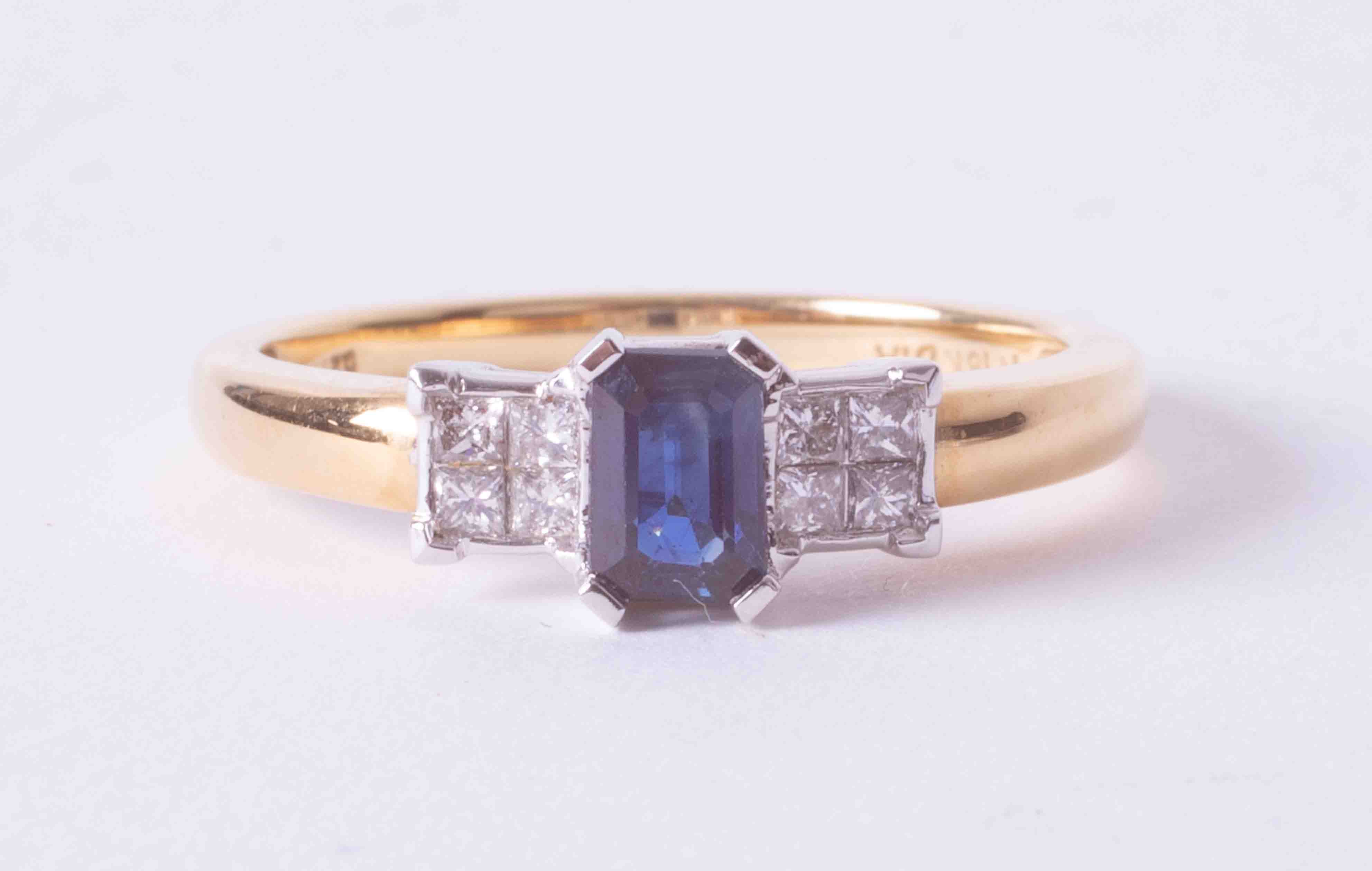 An 18ct yellow & white gold ring set approx. 0.50 carat emerald cut sapphire & 0.21ct total weight