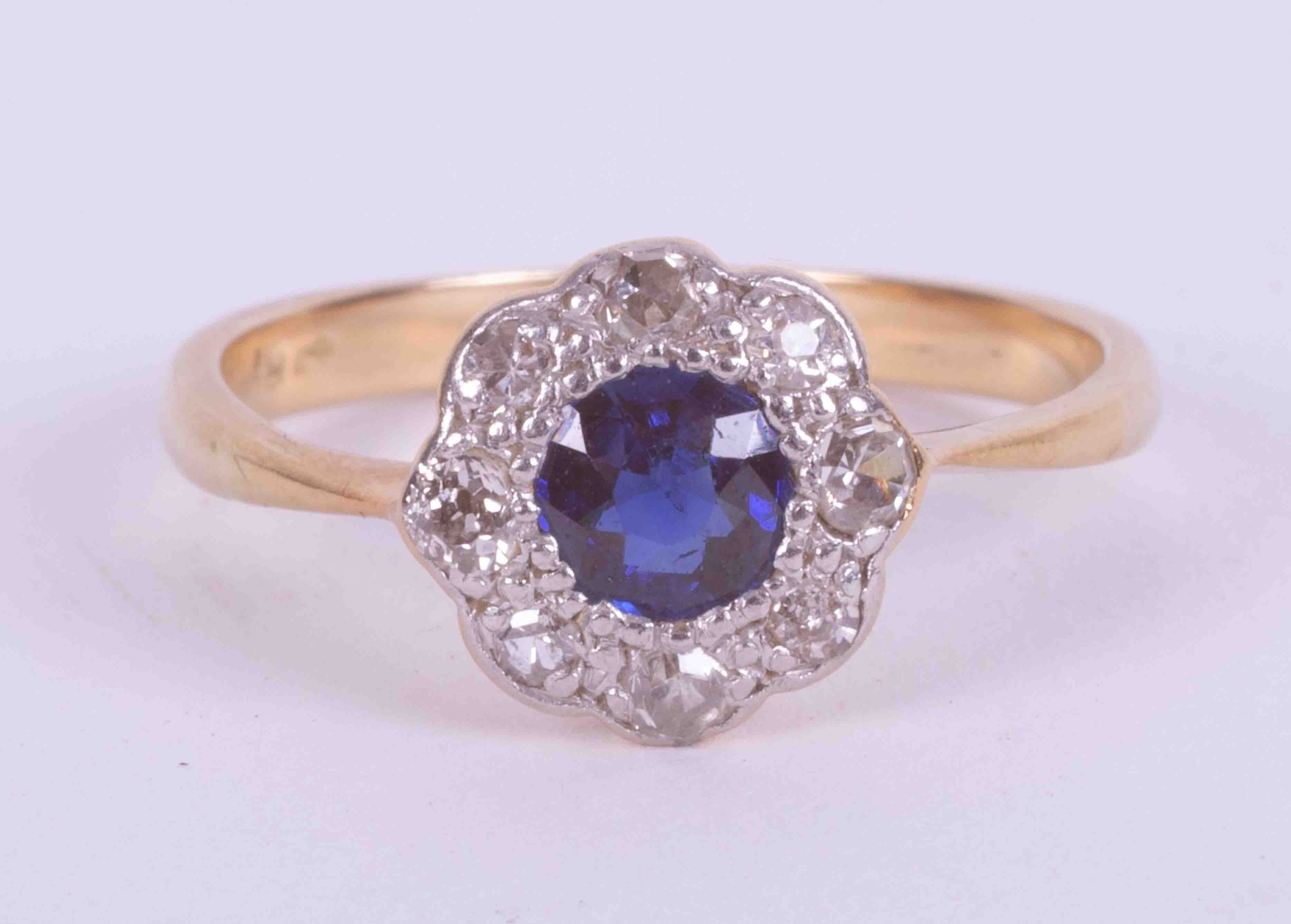 An 18ct yellow & white gold cluster ring set with an old cut round sapphire approx. 0.40 carats