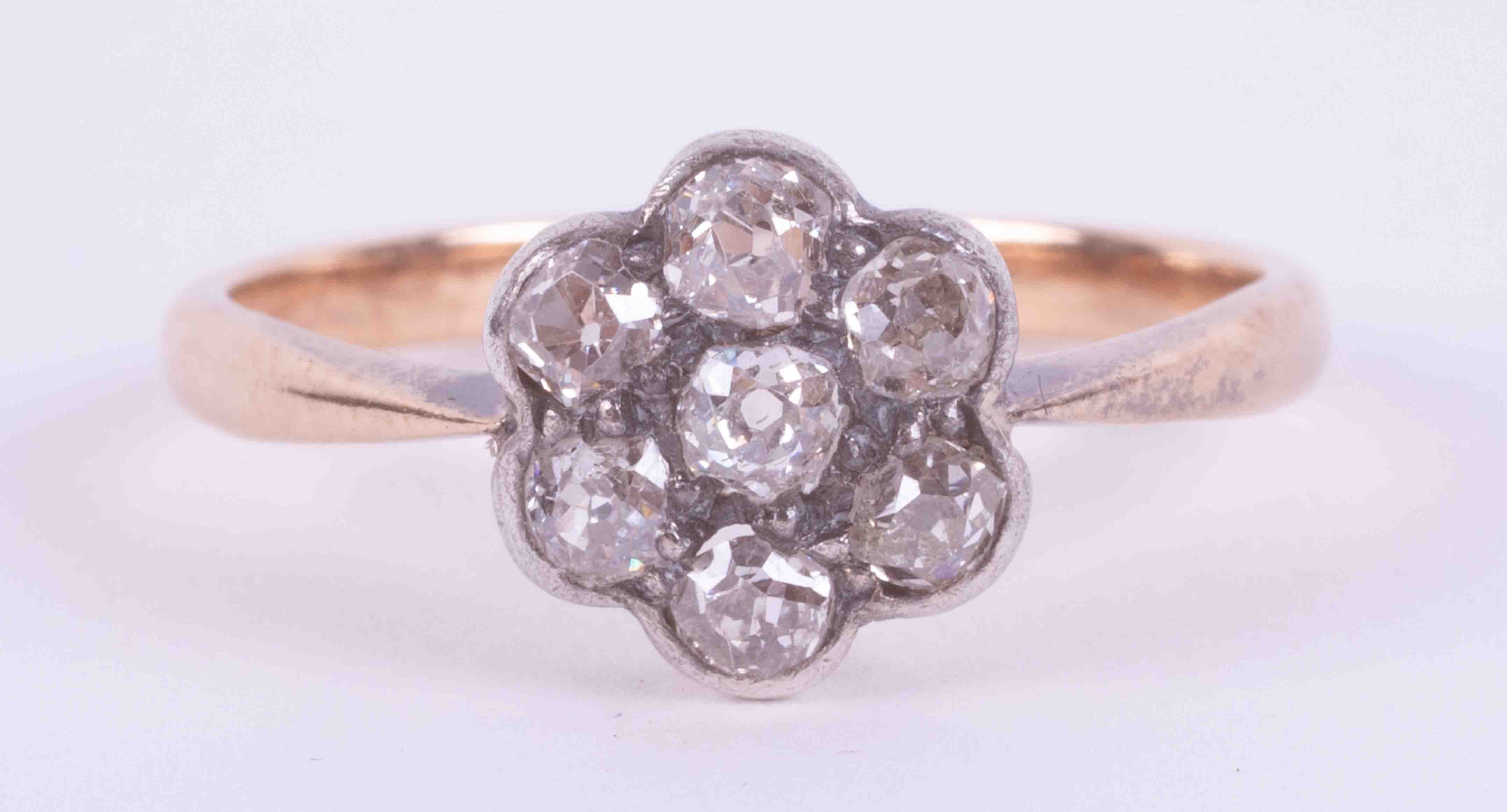 An 18ct yellow & white gold flower cluster ring set with seven old round cut diamonds, approx. total