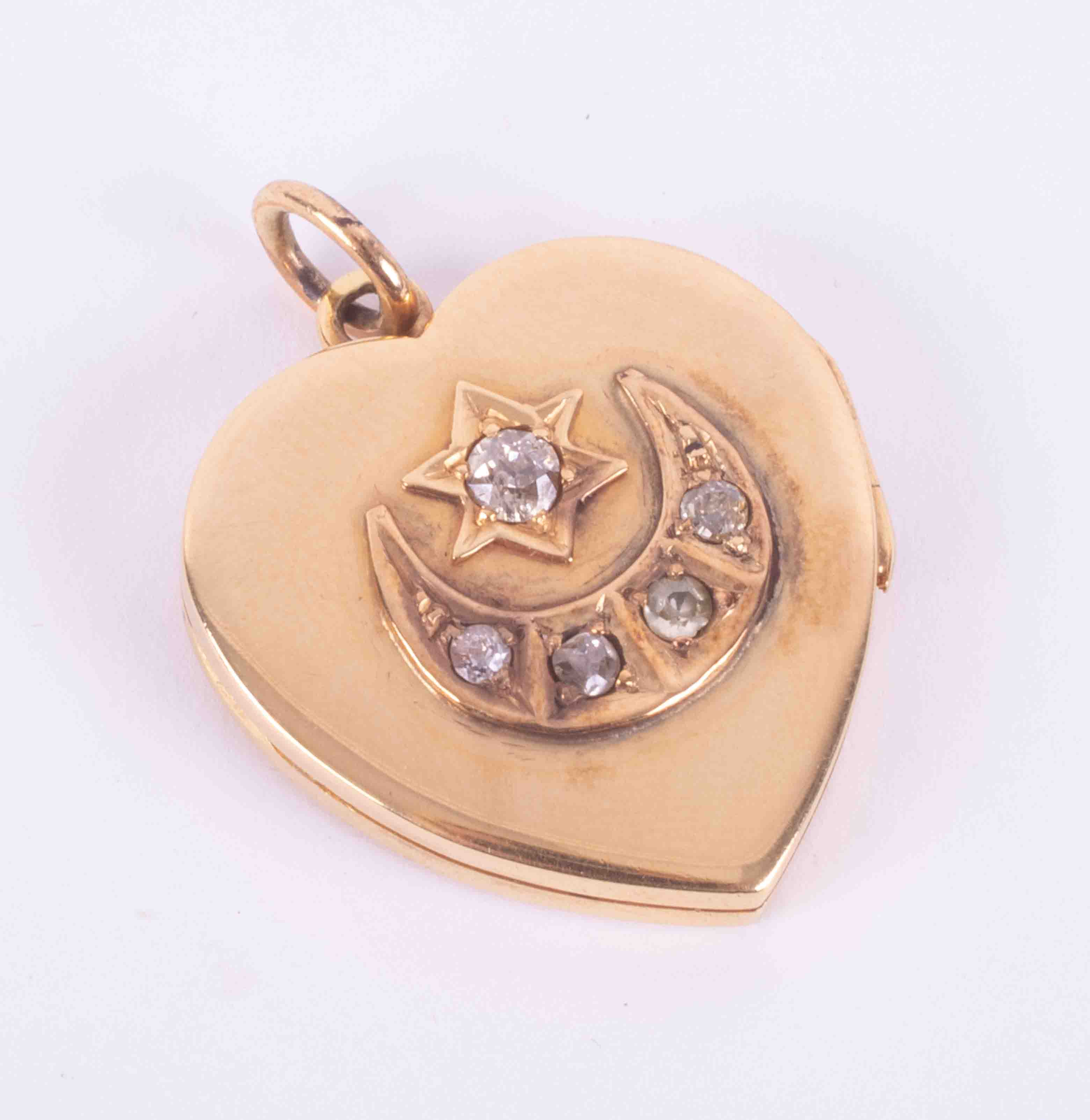 An antique 18ct yellow gold heart locket with a star and moon design set with five old round cut