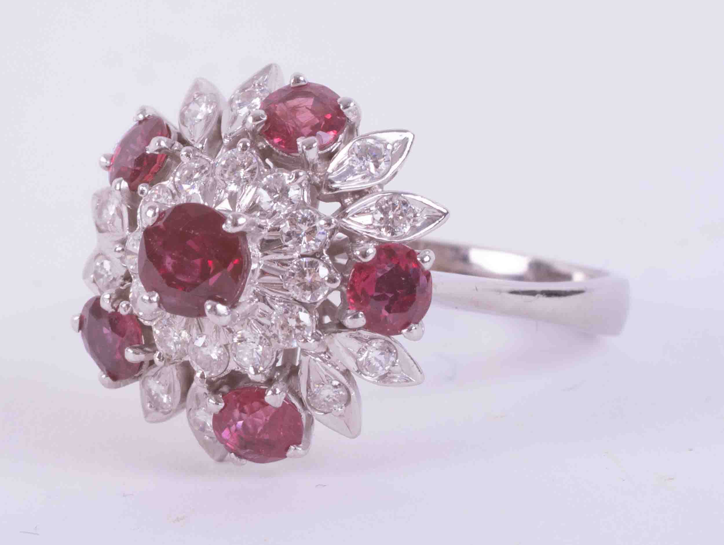 A 14ct white gold flower design cluster ring set with approx. 1.75 carats of round cut rubies