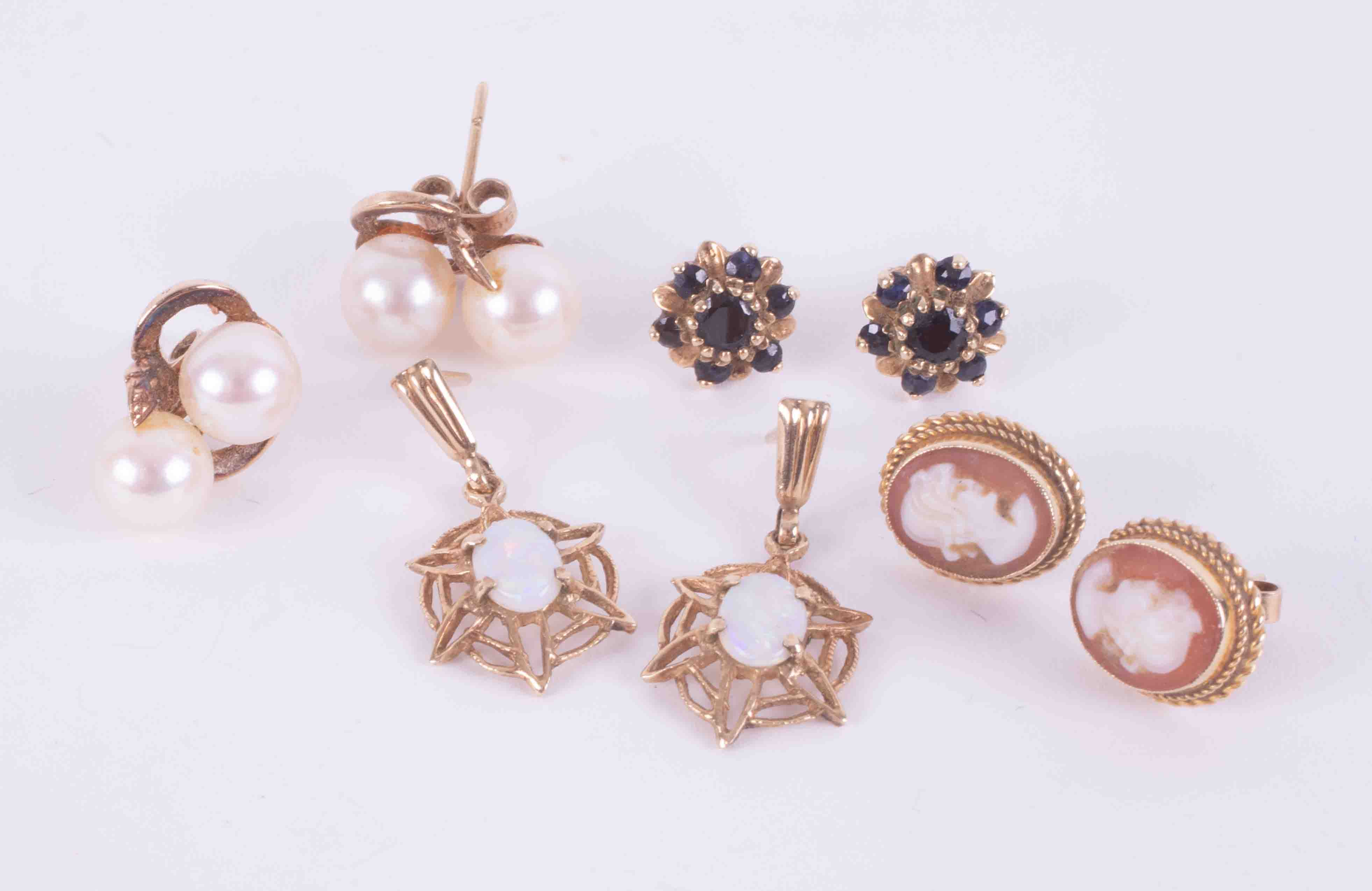 Four pairs of 9ct yellow gold earrings to include a pair of white opal set spider web drop