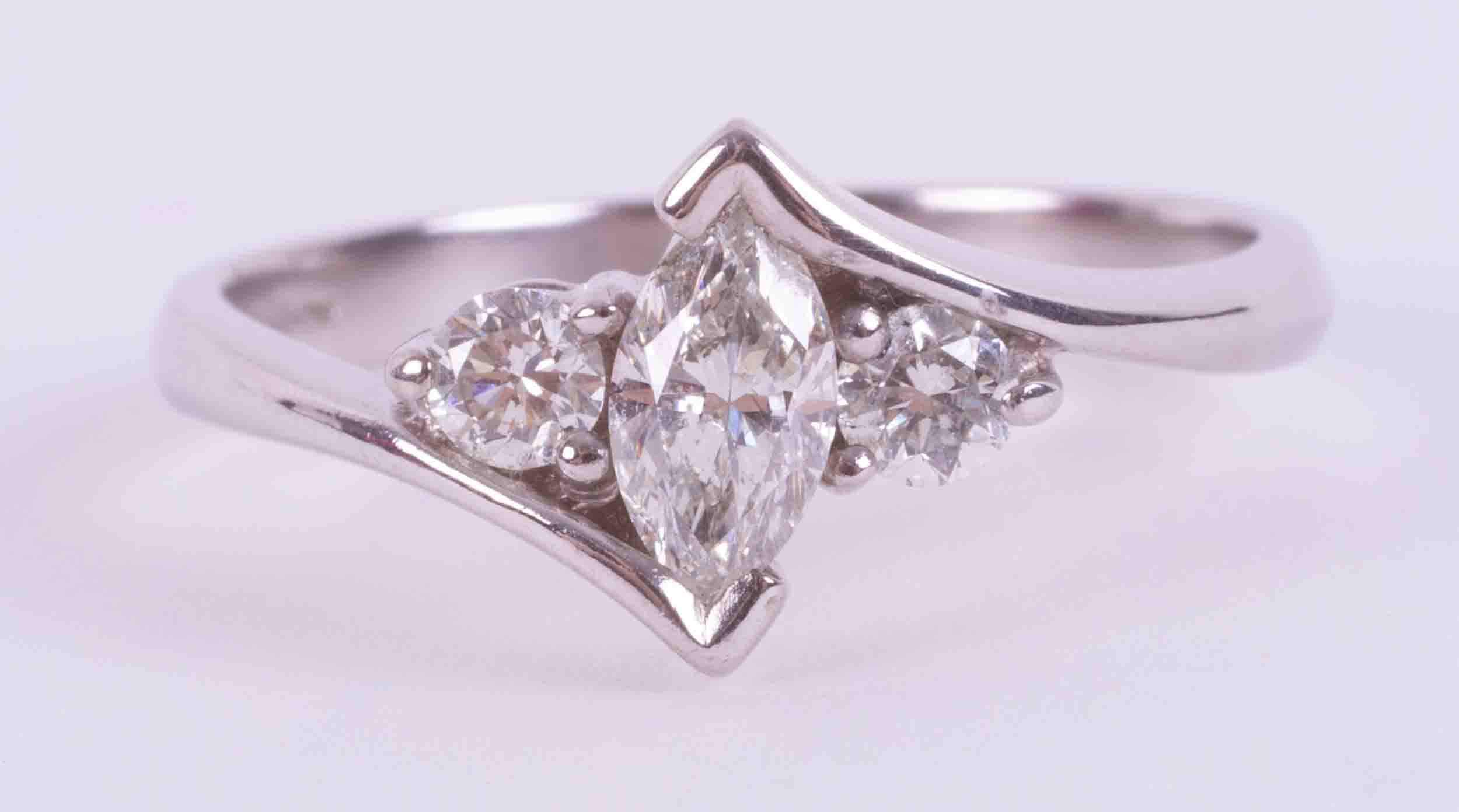 An 18ct white gold cross over style ring set with a central marquise cut diamond, approx. 0.27