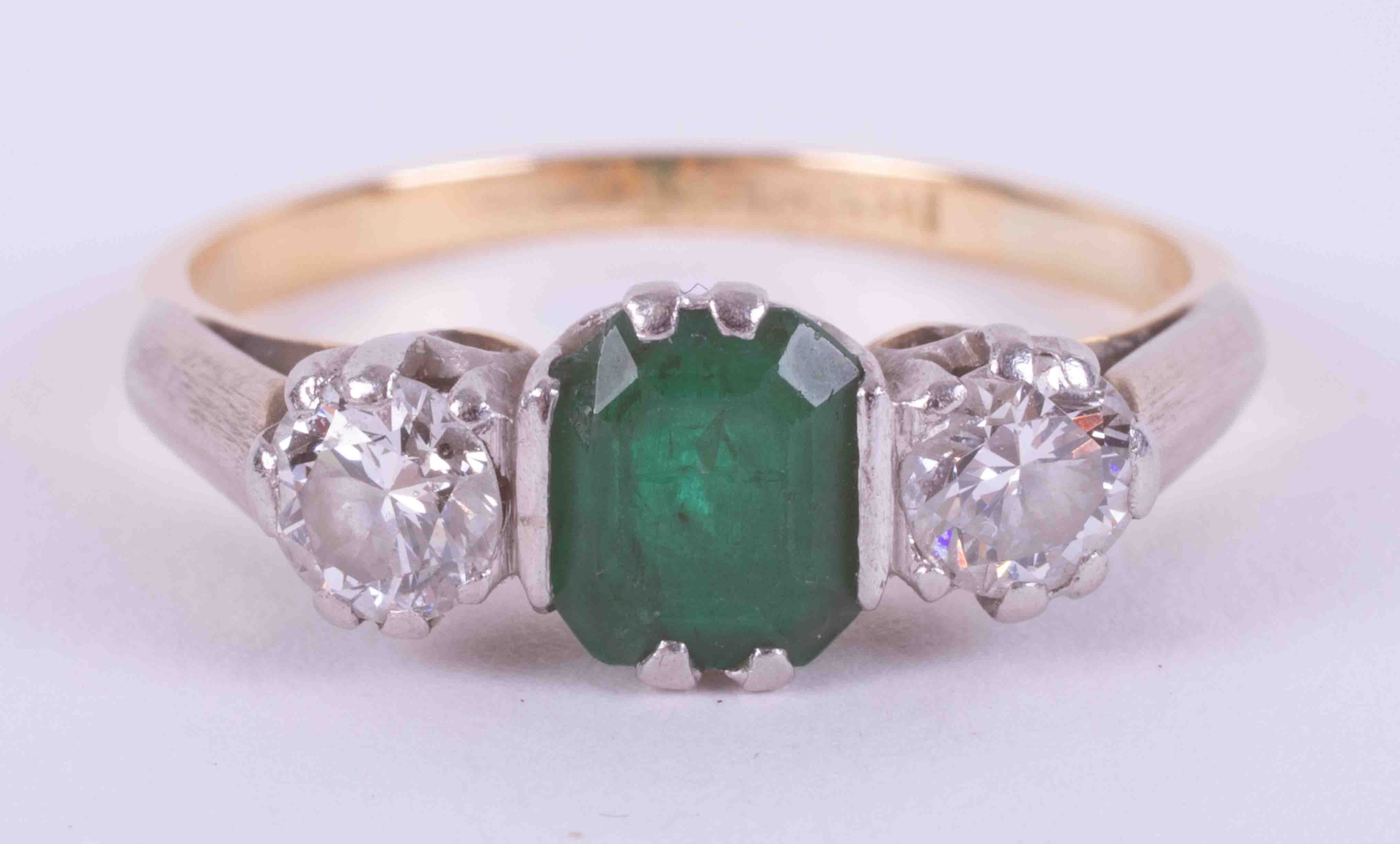 An 18ct yellow gold & platinum three stone ring set with a central emerald cut emerald, approx. 0.50