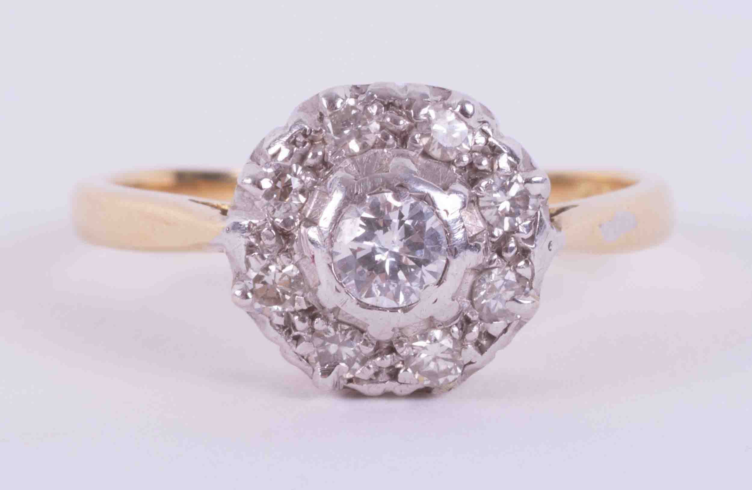 An 18ct yellow & white gold flower style cluster ring set with approx. 0.15 carats of round cut