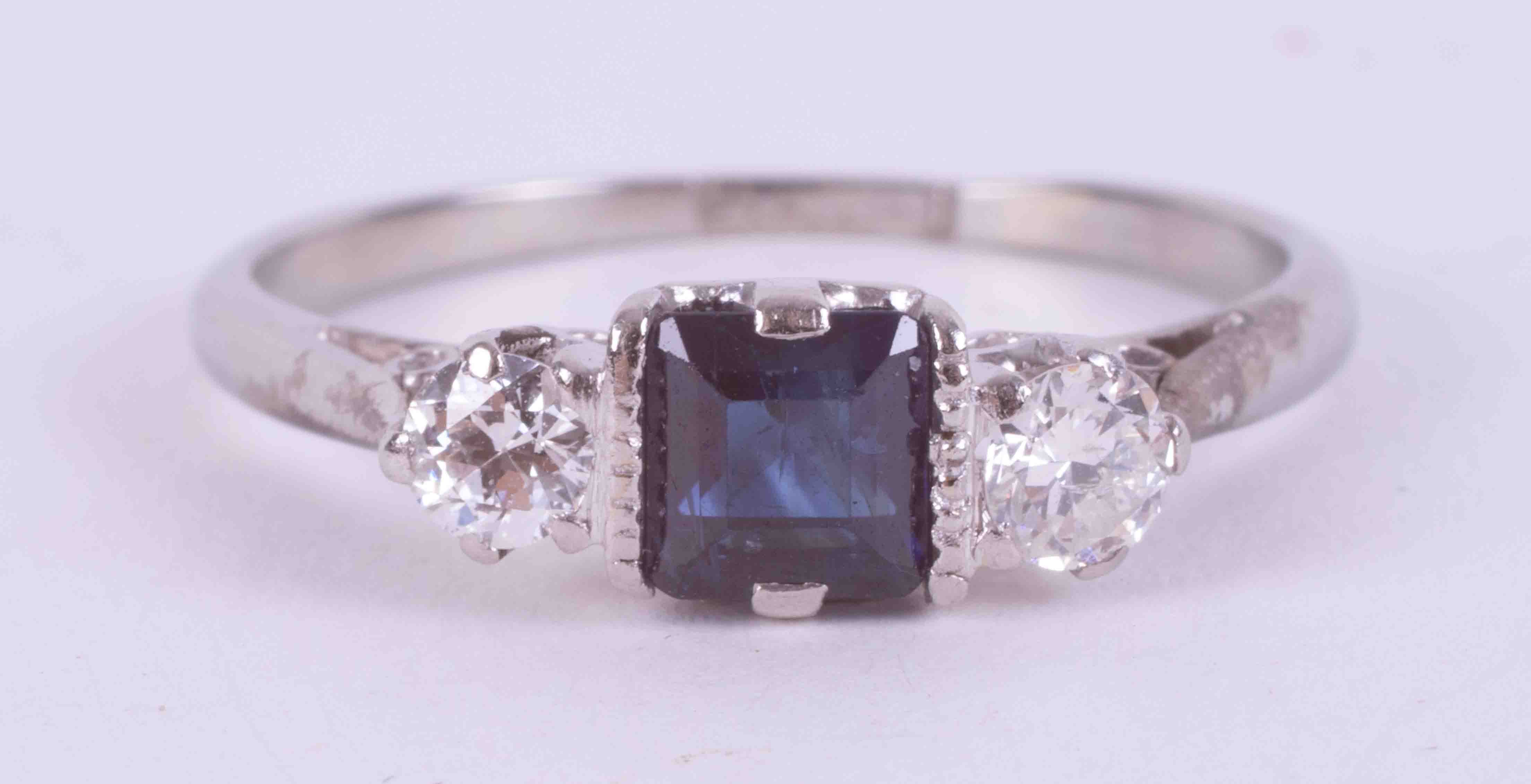 A platinum three stone ring set with a central square cut sapphire, approx. 0.36 carats, with one