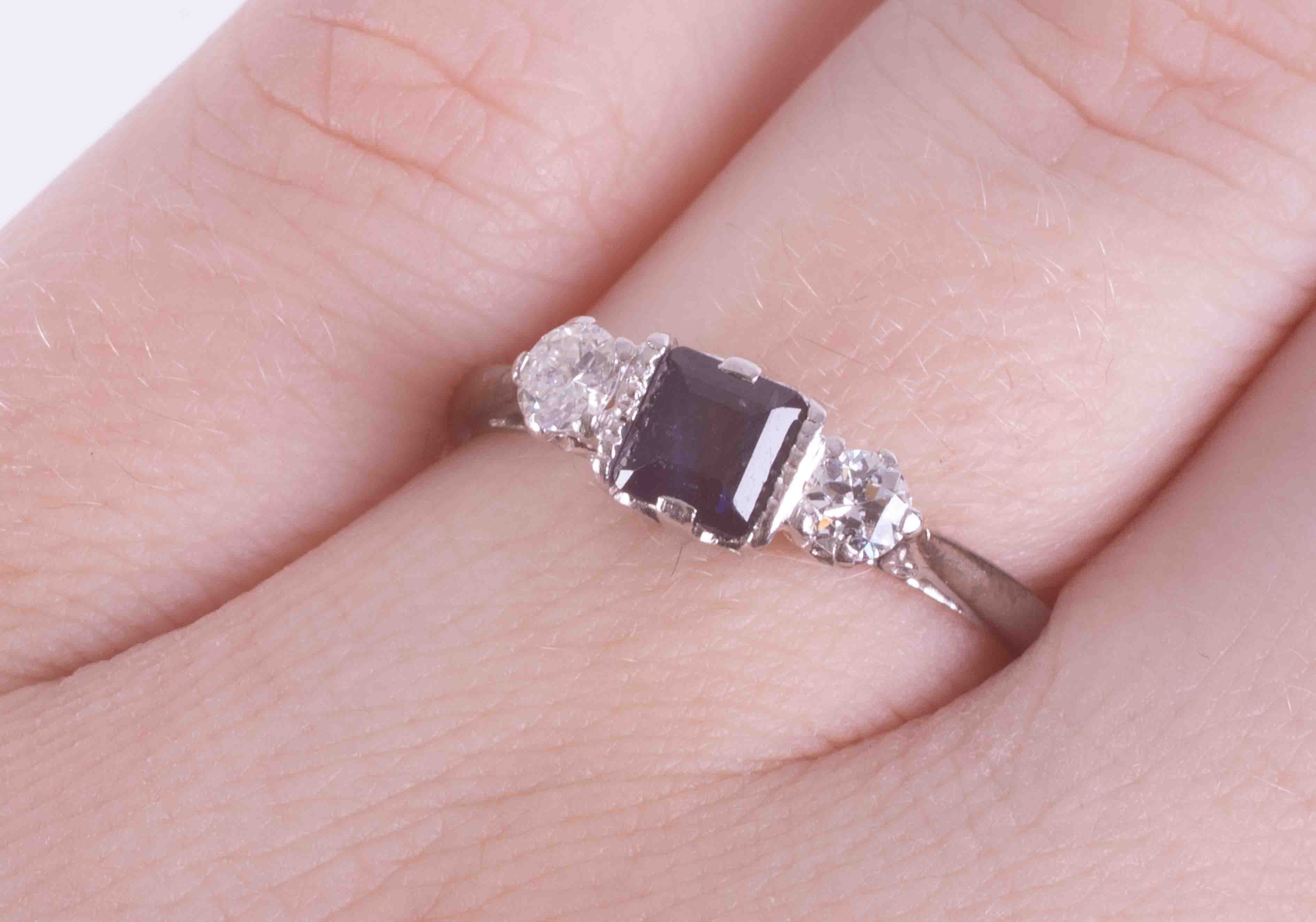 A platinum three stone ring set with a central square cut sapphire, approx. 0.36 carats, with one - Image 2 of 2