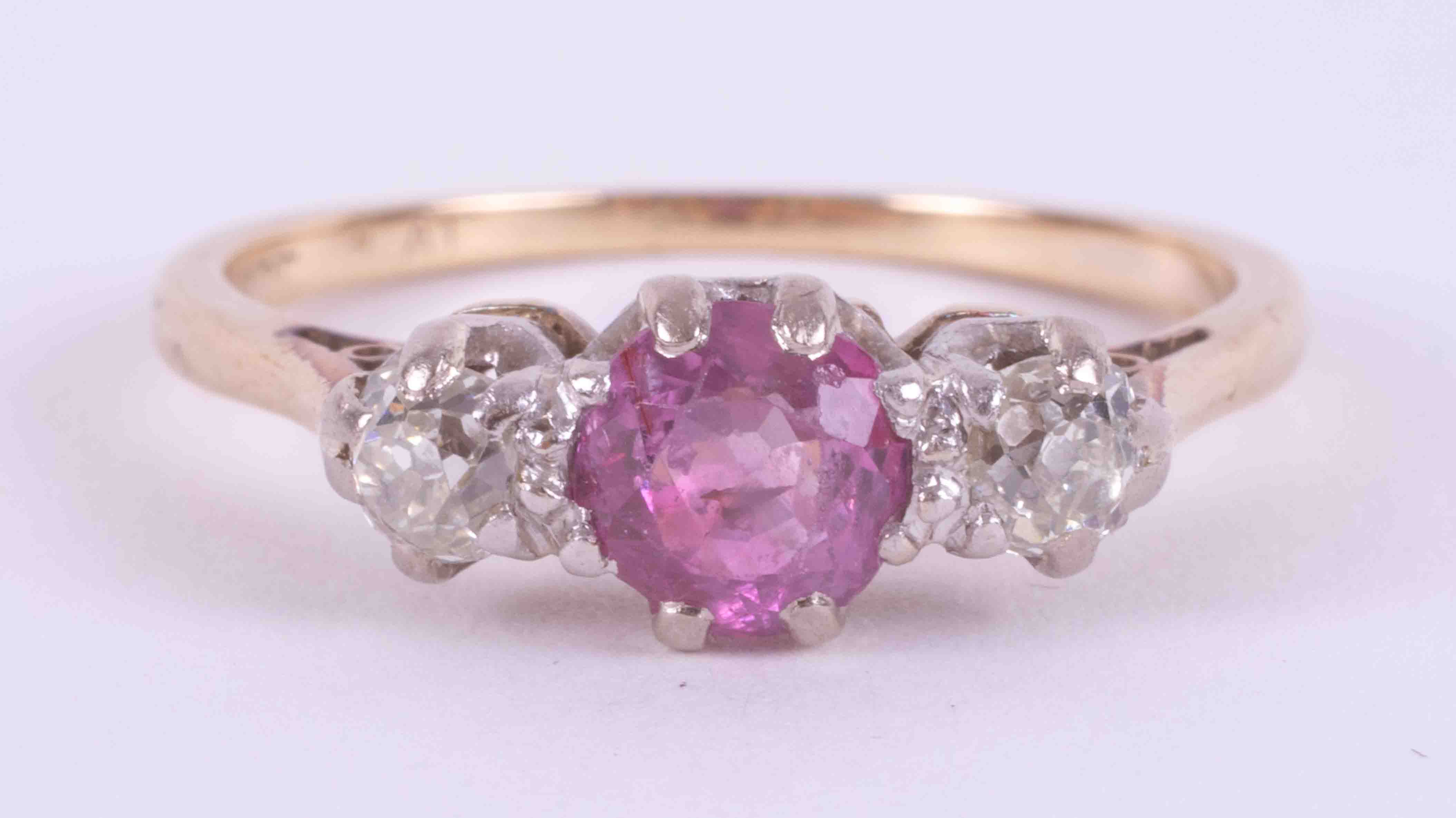 An 18ct yellow gold & platinum three stone ring set with a round cut pink sapphire or ruby? (