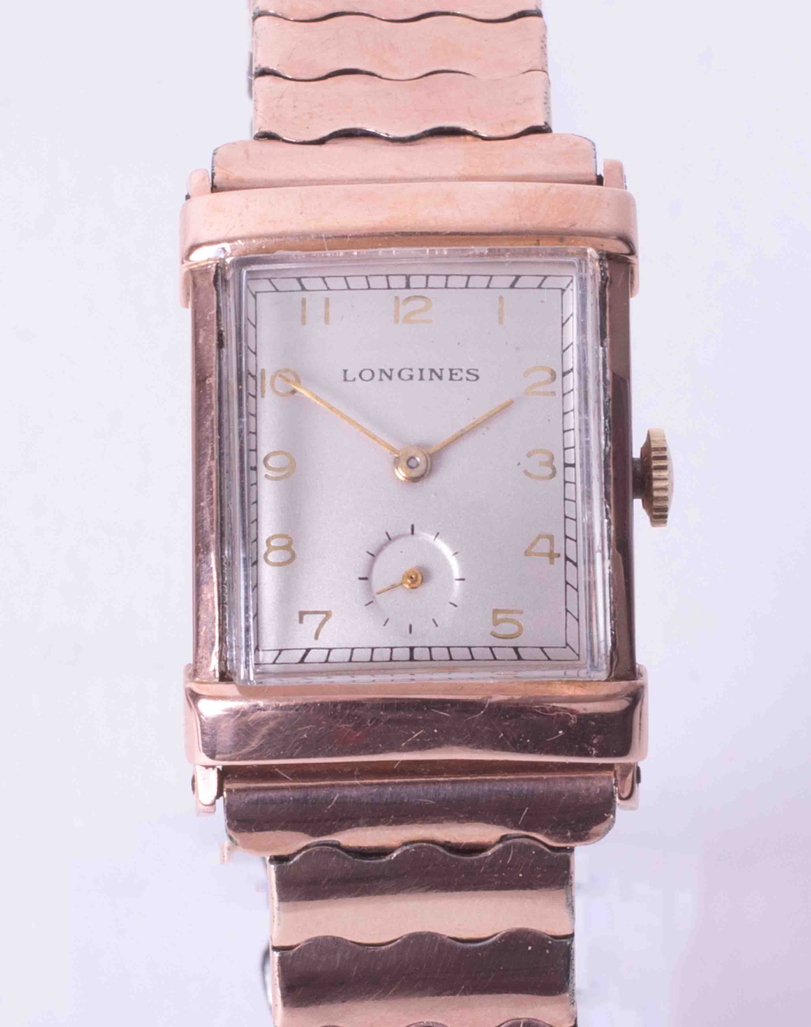 Longines, a gents mid size rectangular cased rose colour (gold filed) wristwatch, integral expanding