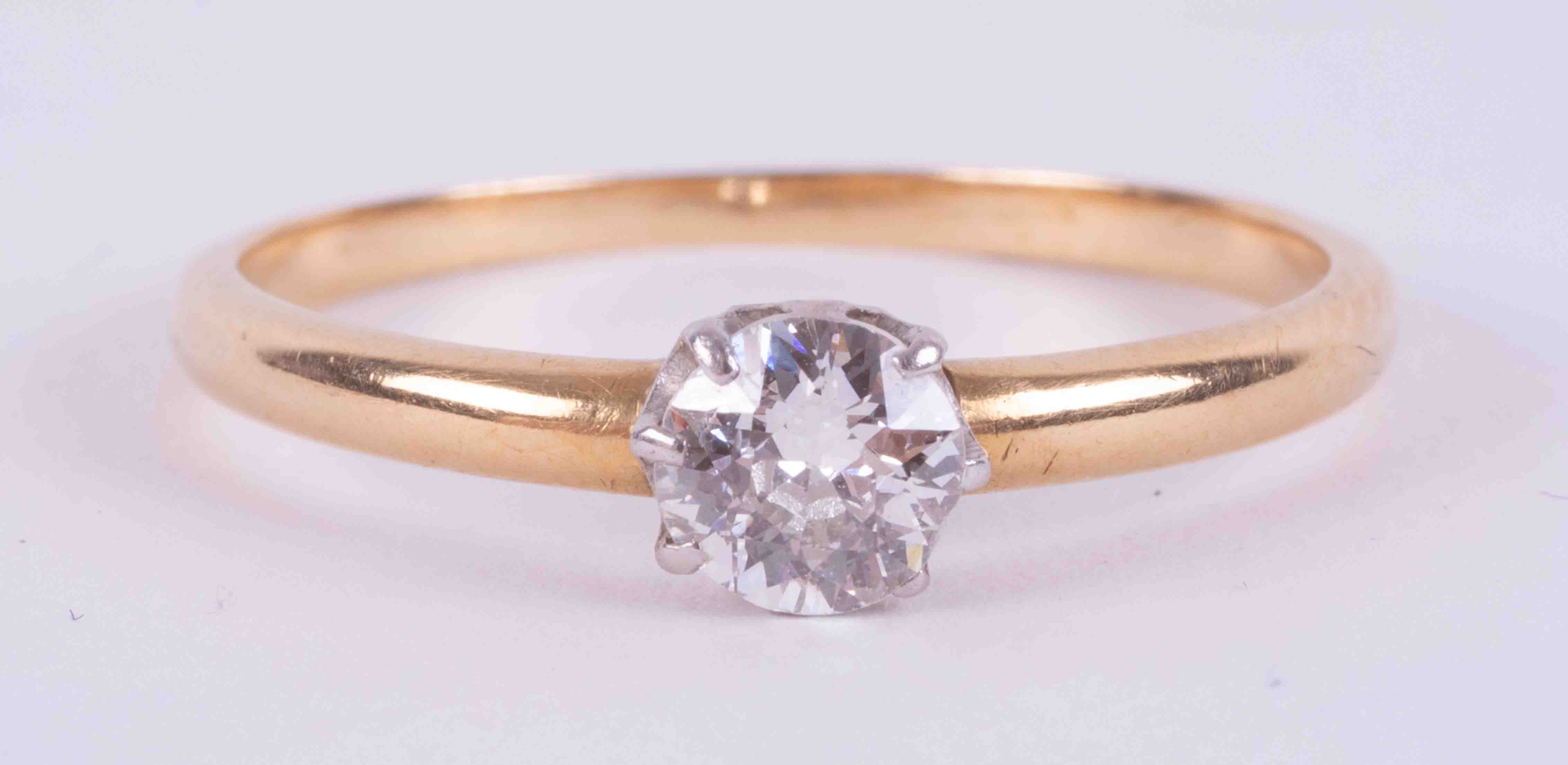An 18ct yellow & white gold (no hallmarks and not tested) solitaire ring set with an older cut round