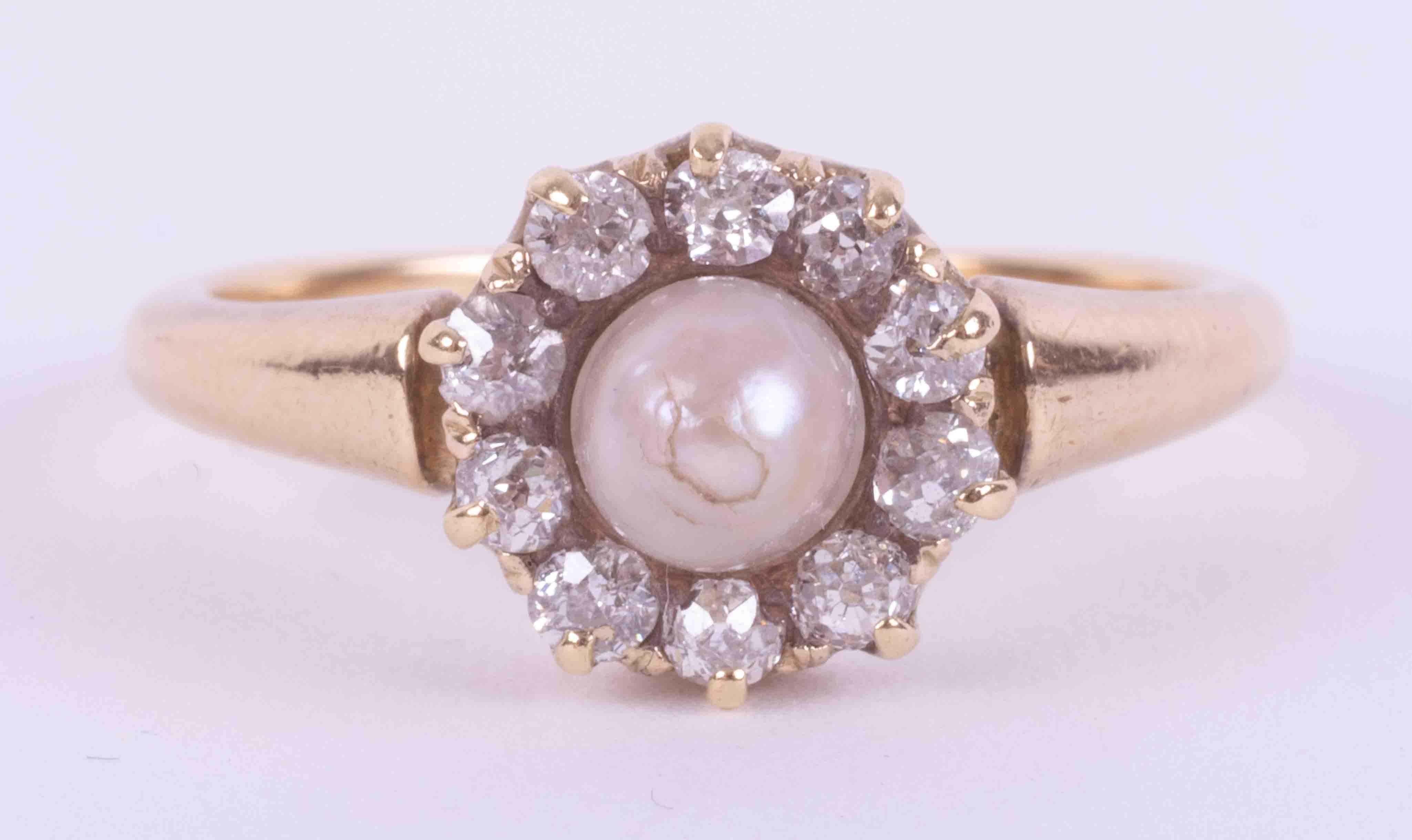 An 18ct yellow gold (not hallmarked or tested) antique ring set with a central pearl surrounded by