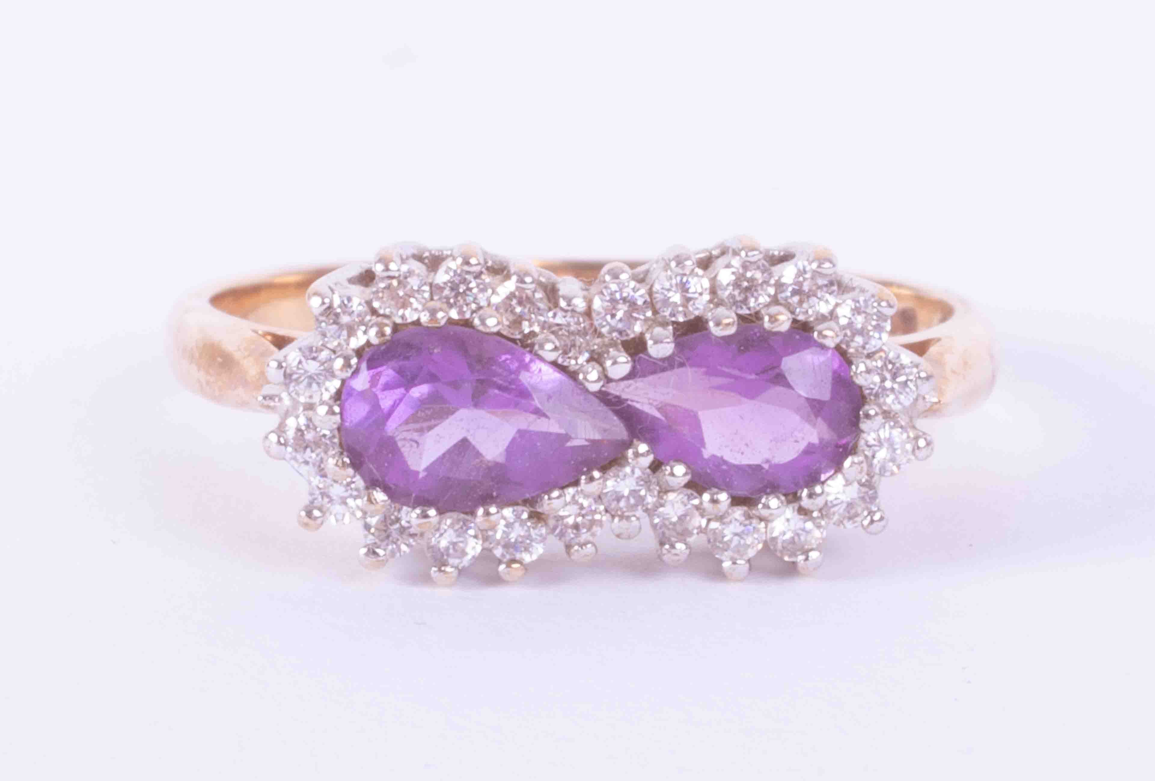 A 9ct yellow & white gold cluster ring set two pear shaped amethysts weight approx. 0.85 carats