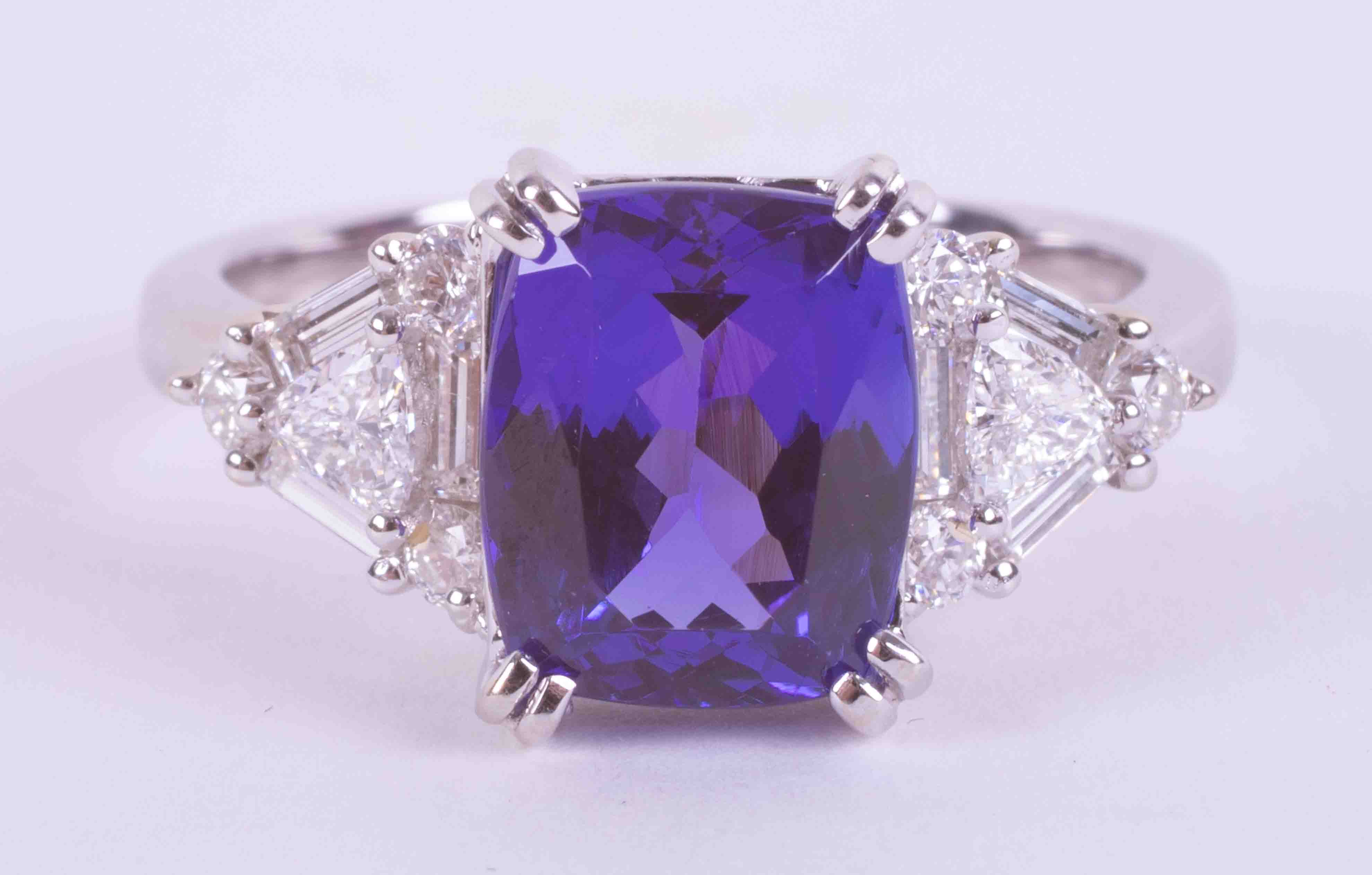 An impressive 18ct white gold ring set with a central cushion cut Tanzanite approx. 3.35 carats, AAA
