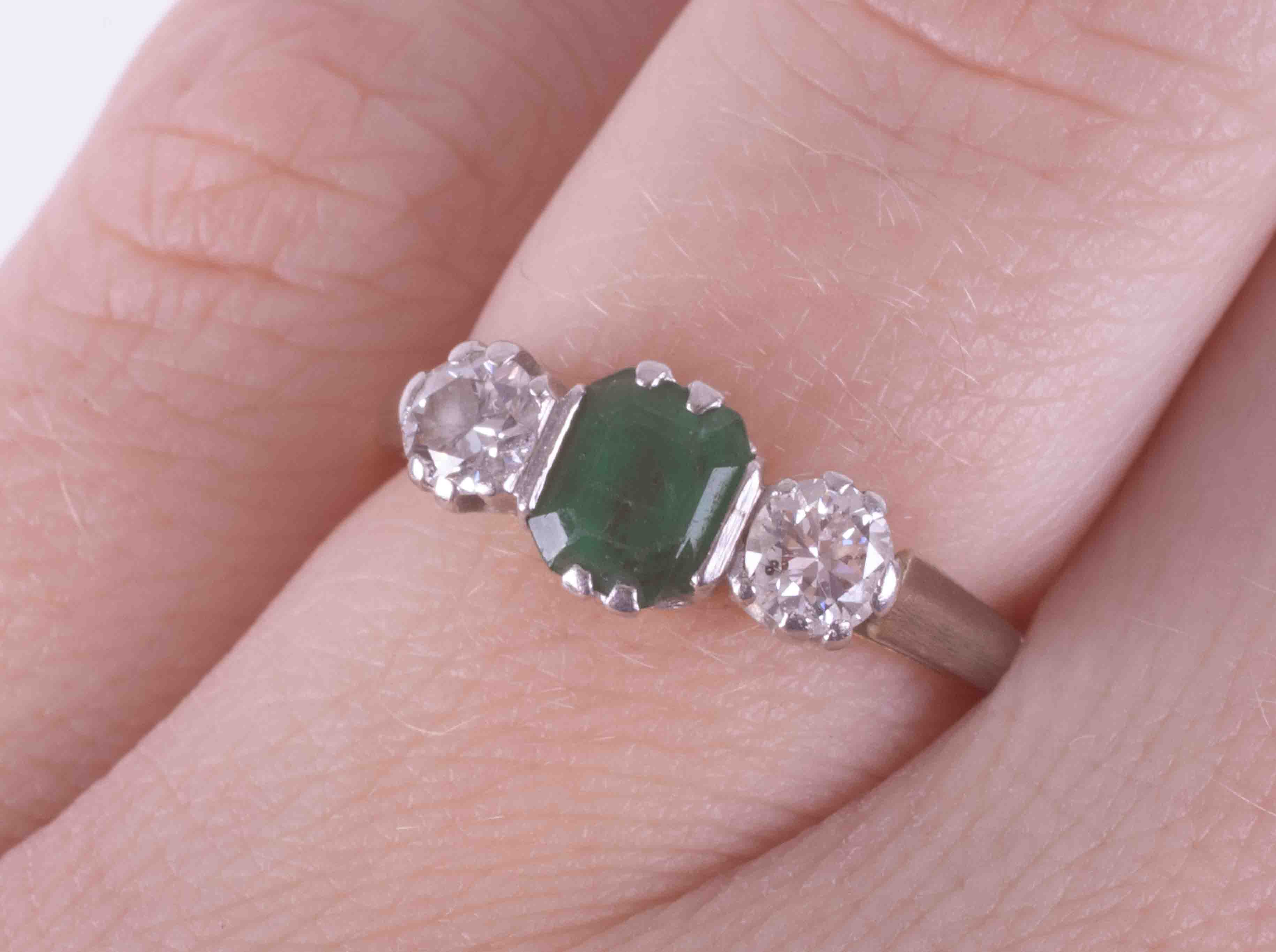An 18ct yellow gold & platinum three stone ring set with a central emerald cut emerald, approx. 0.50 - Image 2 of 2