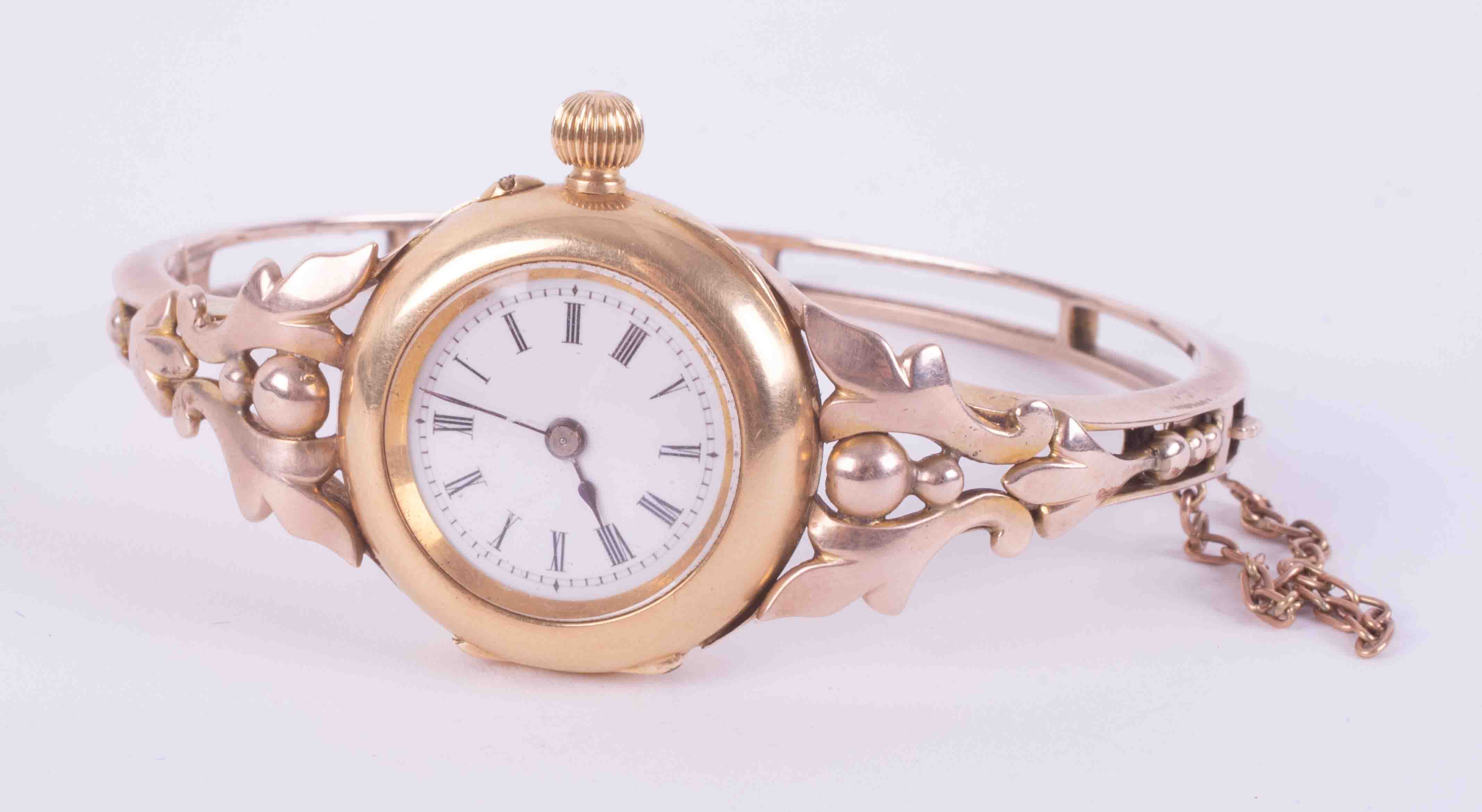 An antique 18ct & 9ct yellow & rose gold ornate bangle watch with push in clasp & safety chain, (