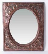 A copper Art Nouveau framed mirror with embossed decoration, 61cm x 51cm.