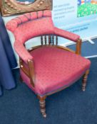 A traditional upholstered and wood framed tub armchair.