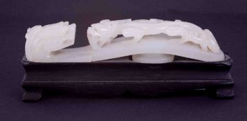 A Chinese carved white jade belt buckle, depicting a dragon on a dragon bridge, length 9cm on a
