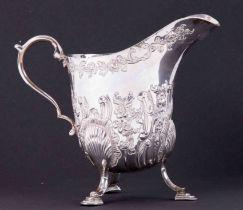 An Irish silver embossed cream jug HM West & Son, Dublin, 234gms, height 12cm.