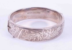 A solid silver bangle, engraved, with safety chain, approx 25.60gms.