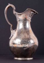 A Victorian silver cream jug, London, makers mark JH? With chased flower decoration, approx