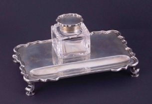 An Edwardian silver inkwell and stand, the oblong tray with Chippendale style edge on scrolled