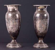 A pair of silver bud vases with hammered effect.