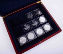 Nine silver crowns, Monarchs of England, each 28.7gm in a mahogany effect case.