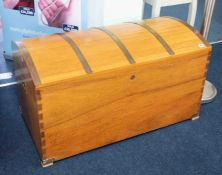 A large teak chest with planked and brass strapped dome lid, recessed brass military handles,