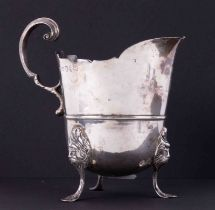 Newcastle silver cream jug on three feet with sterilised face decoration, height 12.5cm, 250gms.