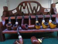 Nine vintage tobacco pipes including K & P, Torino, and a wooden pipe rack carved with initials