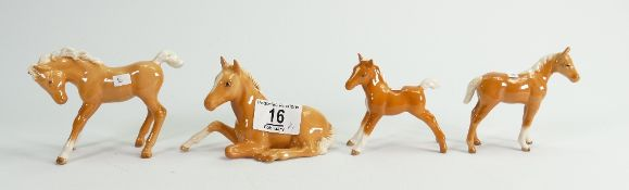 Four Beswick palomino foals: to include lying down, small thoroughbred,
